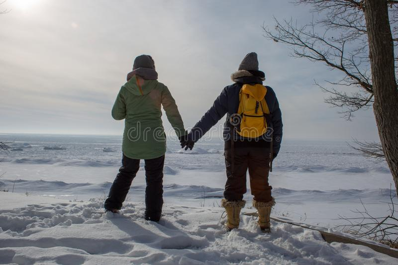 Two women holding hands on a frozen lake shore. Two women holding hands with backs turned on frozen lake shore royalty free stock image