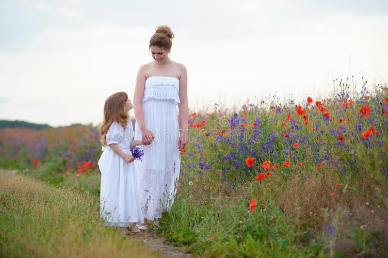 Two women holding hands outdoors. Two women in dresses walking o royalty free stock images