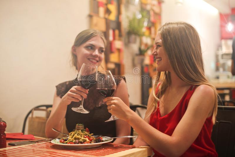 Two Women Holding Long-stem Wine Glasses With Red Liquid stock images