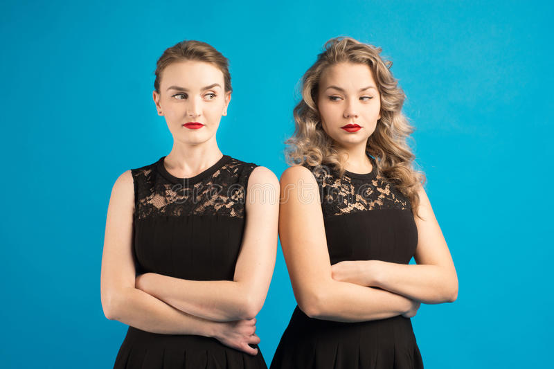 Two women in identical dresses are angry at each other. Two women in identical black dresses are angry at each other stock photo