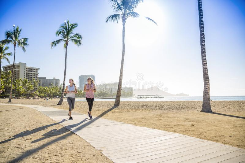 Two Women jogging on the beach boardwalk between two palm trees. Great fitness photo of women working out. Copy space in the blue sky and sand royalty free stock photo