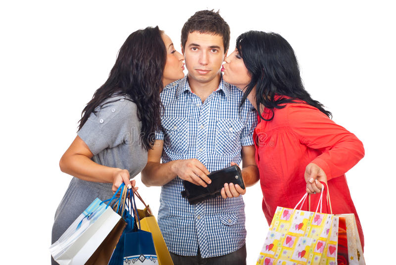 Two women kiss sad man to give them money royalty free stock images