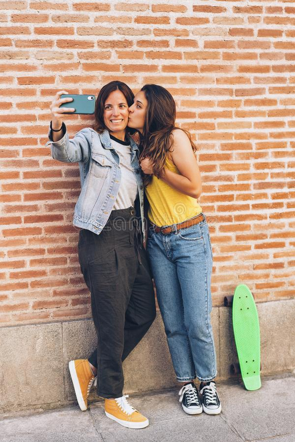 Two women kissing and making selfie. Tolerance and same sex relationship concept.  royalty free stock photo