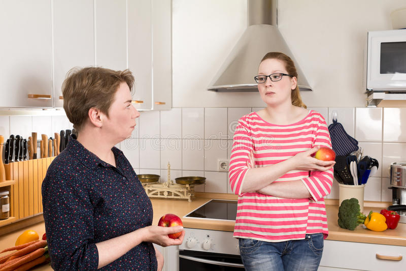 Two women kitchen bad mood. Young and old women in kitchen with two apples in their hands and bad mood royalty free stock photos