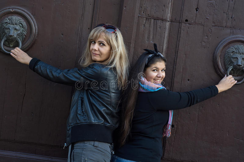 Two women knocking on the door with knockers royalty free stock photo