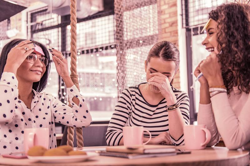 Two women laughing after their friend word explanation while sitting in bakery royalty free stock photo