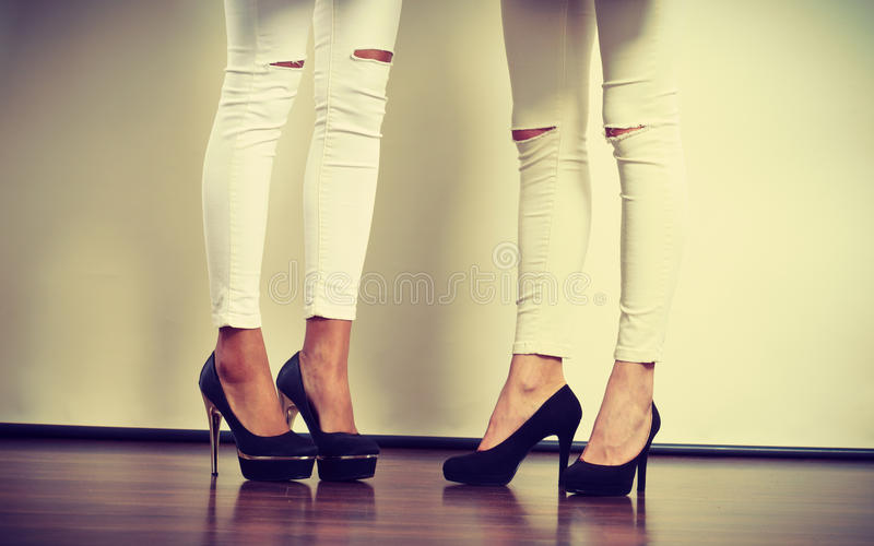 Two women legs presenting high heels. Fashion, clothes, clothing accessories, trendy outfits concept. Two women legs presenting high heels wearing white slim royalty free stock image