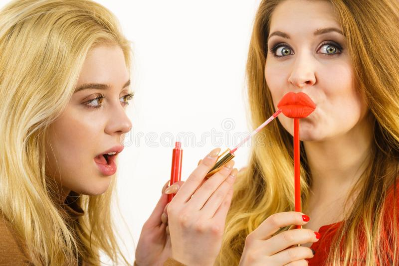Two women and lip product. Two women having fun while doing make up. Friends holding lip gloss or lipstick and fake lips on stick stock photography