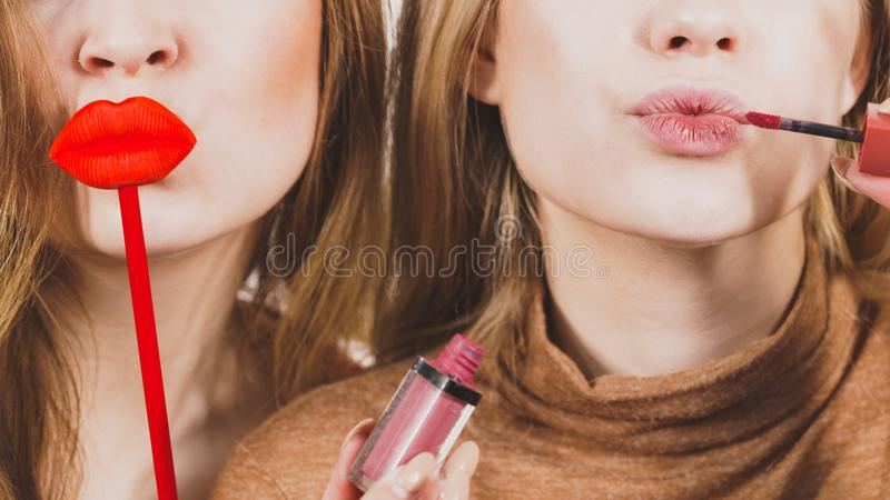 Two women and lip product. Two women having fun while doing make up. Friends holding lip gloss or lipstick and fake lips on stick stock photos