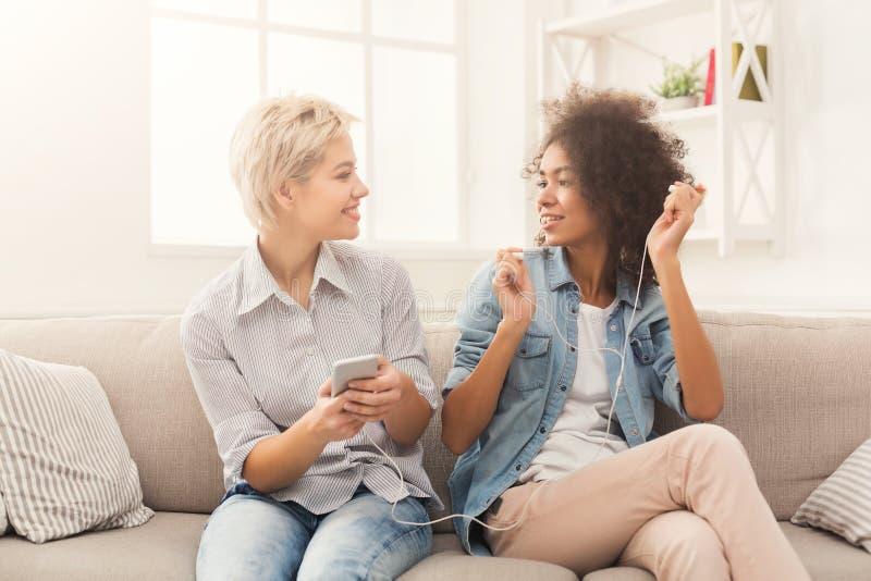 Two women listening music and sharing earphones stock photo