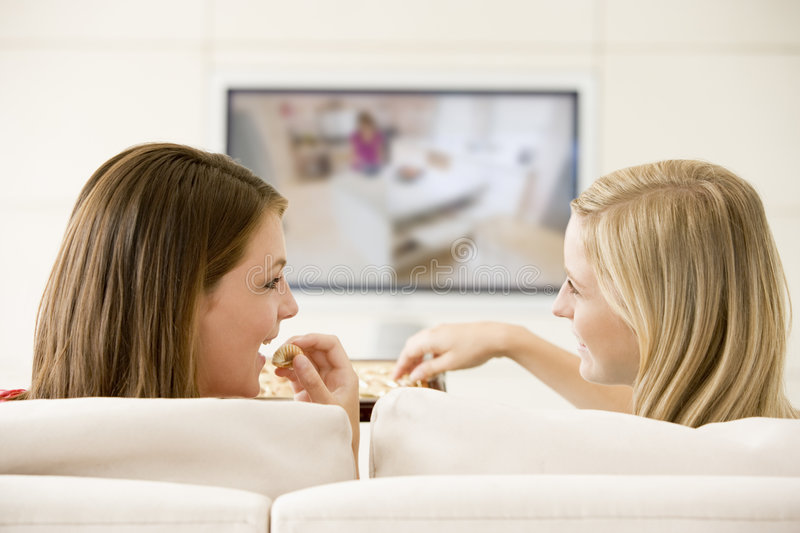Two women in living room watching television stock photo