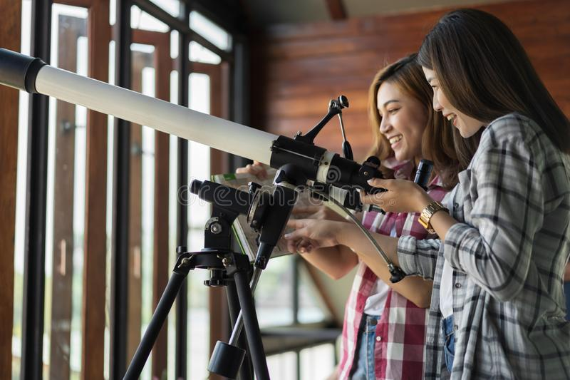 Two woman looking through telescope. Two women looking through binoculars or telescope stock photos