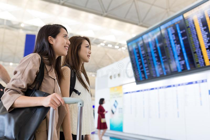 Two women looking at the flight number board. Beautiful young asian woman stock images