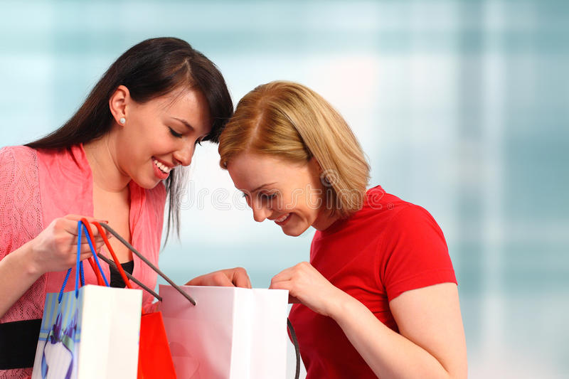 Two women looking inside shopping bags stock image