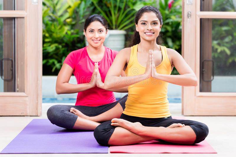Two women in lotus position during yoga practice. Two young women sitting on mats in lotus position during yoga practice indoors royalty free stock photo