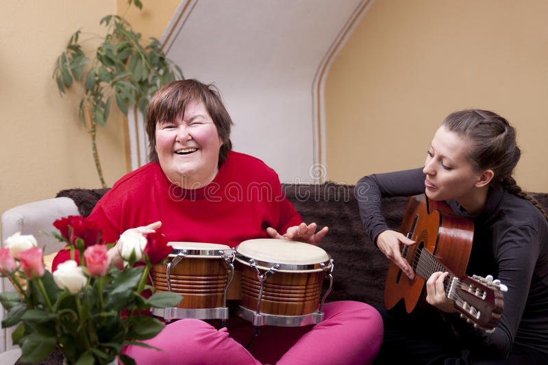 Two women make a music therapy stock photography