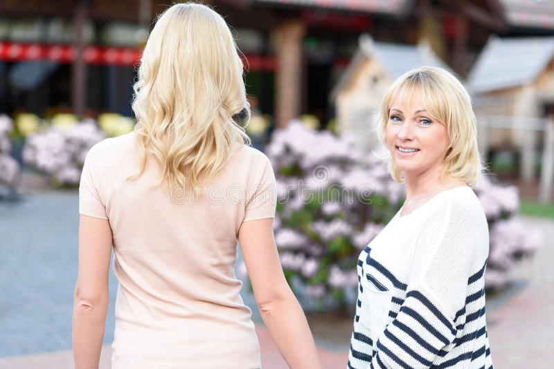 Two women making walk in city. Senior mother is walking with her daughter outdoors. She is looking at camera and smiling royalty free stock photography