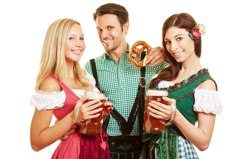 Two women and man with beer at. Two women and men with beer and pretzel at Oktoberfest in Bavaria stock photography