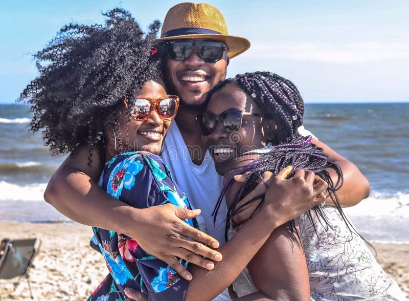 Two Women With Man Hugging by the Sea royalty free stock photos