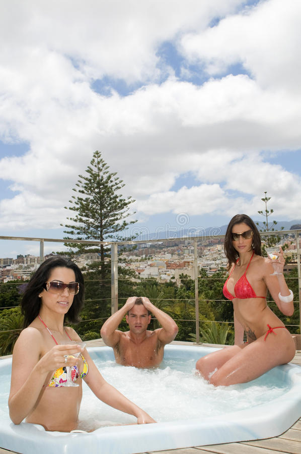 Two women and man relaxing in an outdoor jacuzzi royalty free stock photos