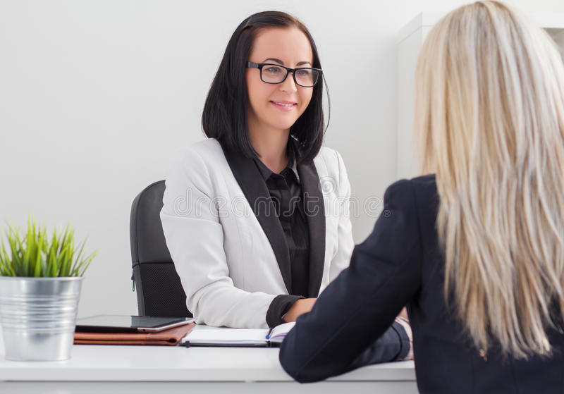 Two women meeting in the office. Two young women meeting in the office royalty free stock photos