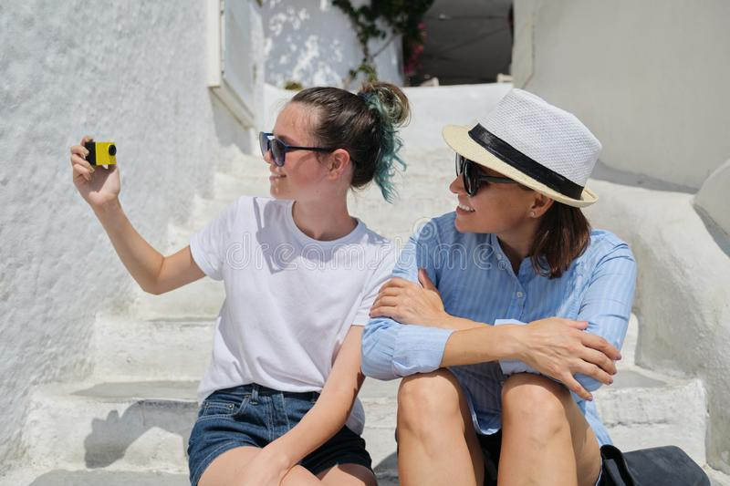 Two women mother and daughter teenager traveling together and recording video vlog royalty free stock photo