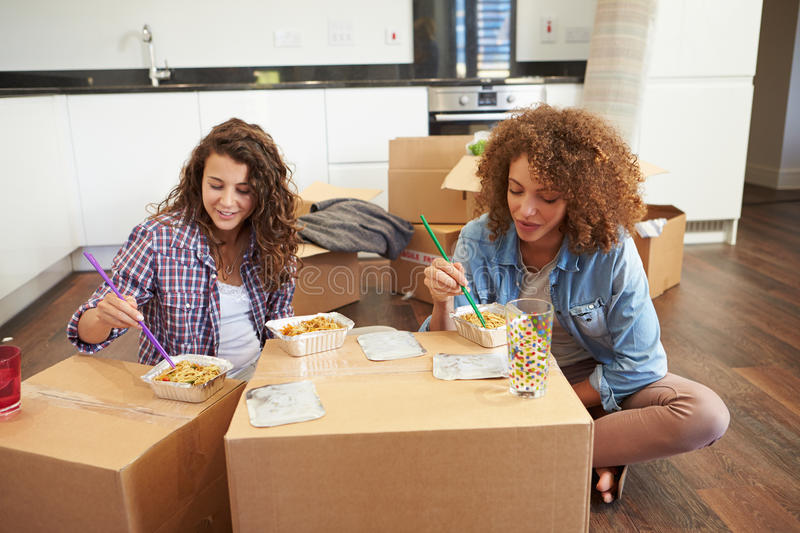 Two Women Moving Into New Home Enjoying Takeaway Meal stock images