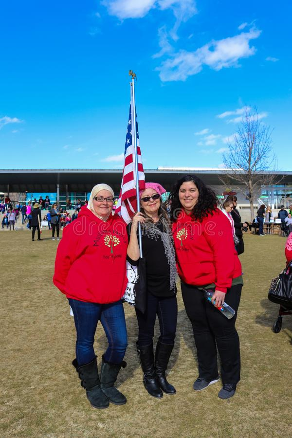 Two women with Muslims 4 Mercy Sweatshirts standing with woman in hat with American Flag at Womens March in Tulsa Oklahoma U royalty free stock photos