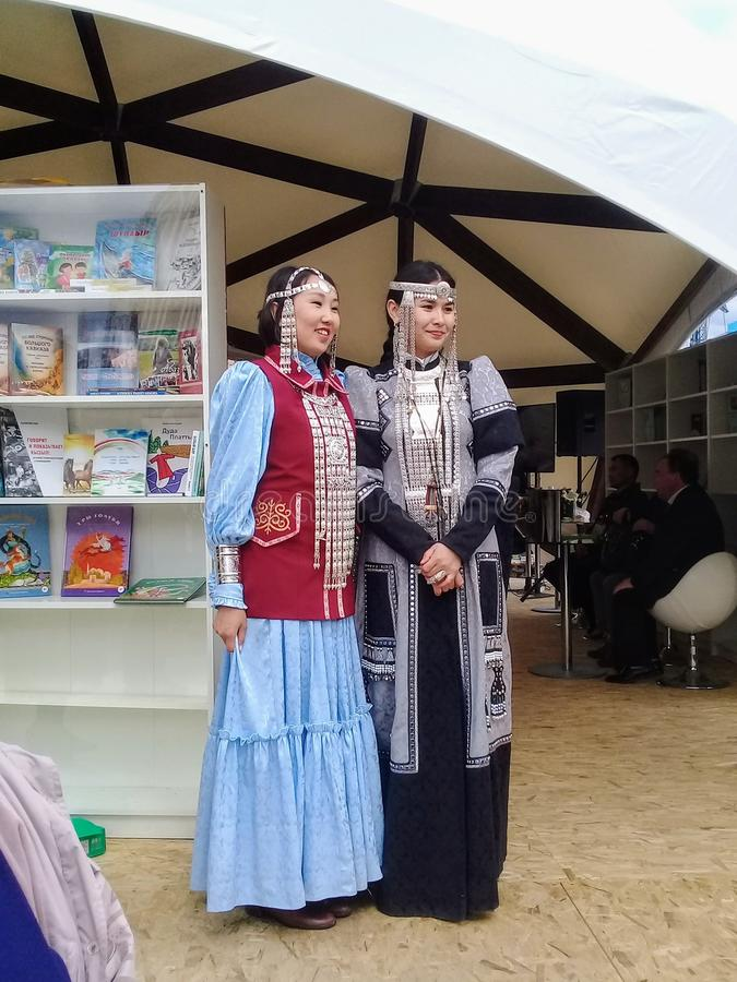 Two women in a national costume posing at a book fair held in Moscow. stock photo