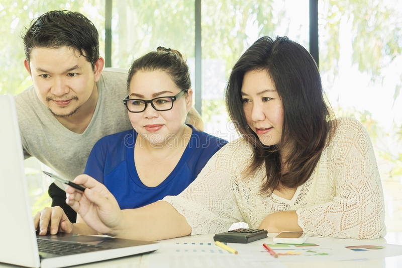 Two women and one man are working with at computer royalty free stock image