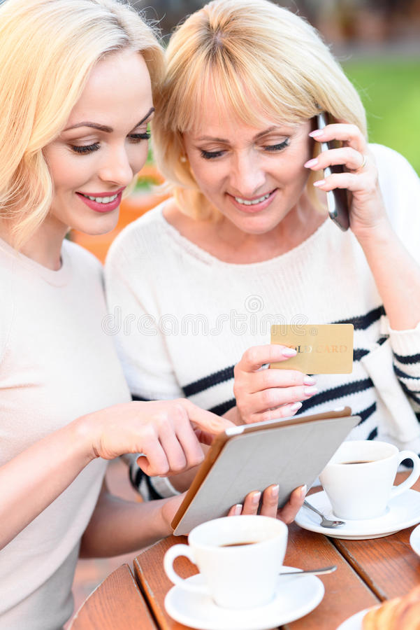 Two women ordering purchase in internet royalty free stock photography