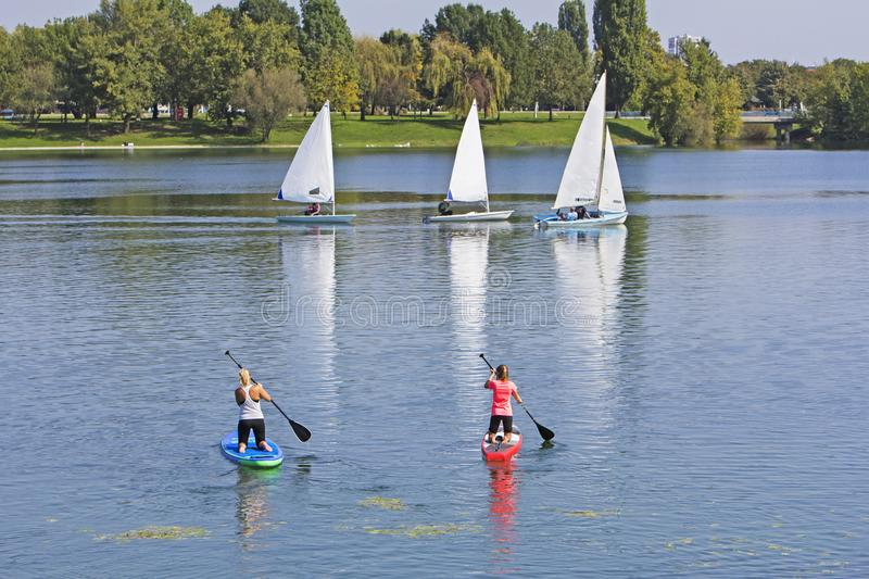 Two women on paddle board and three boat sailling royalty free stock photos