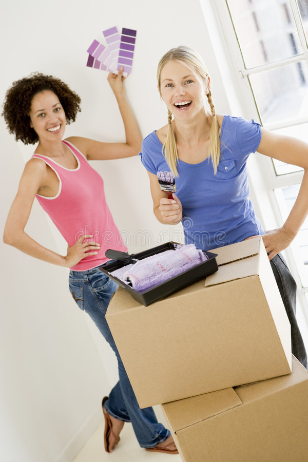 Two women with paint swatches in new home. Smiling stock image