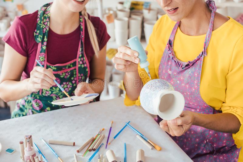 Two women painting own ceramic tableware in DIY workshop. With brushes stock photography