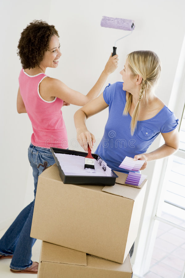 Two women painting room in new home smiling. At each other stock photography