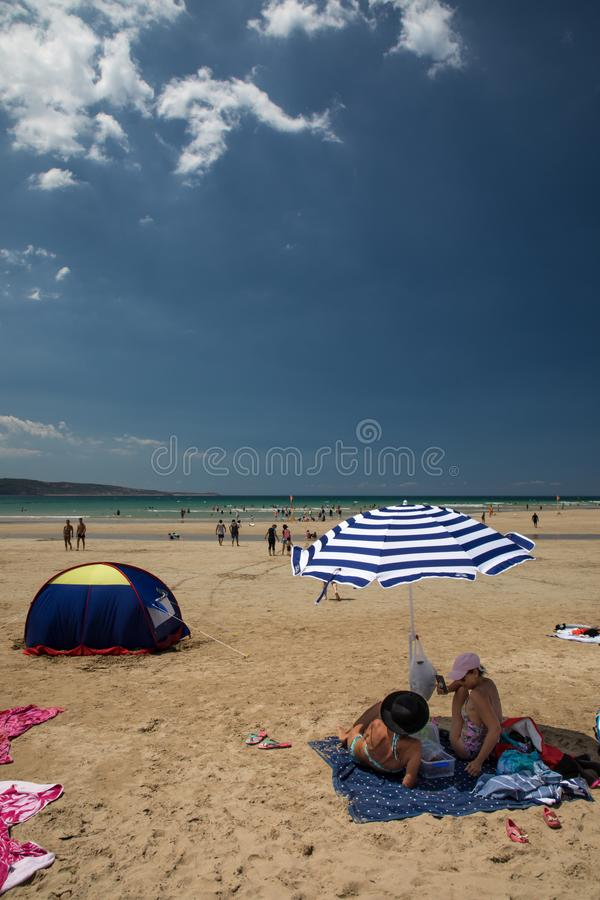 Two women people sitting under a blue and white beach umbrella against a bright blue sky stock photo