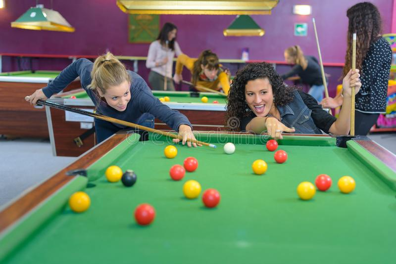 Two women playing pool stock photos