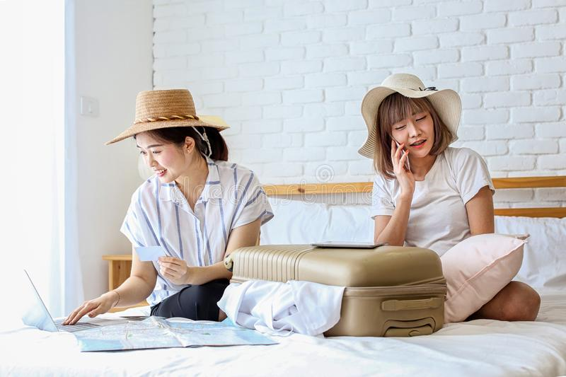 Two women are preparing to travel. Happy young friends packing clothes put in suitcase on bedroom. Female using computer laptop. Planning travel information stock image