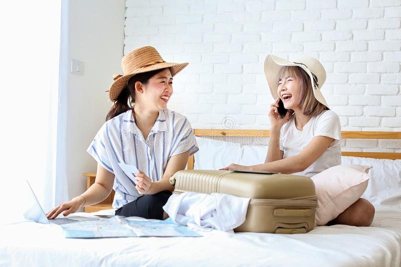 Two women are preparing to travel. Happy young friends packing clothes put in suitcase on bedroom. Female using computer laptop. Planning travel information royalty free stock photography