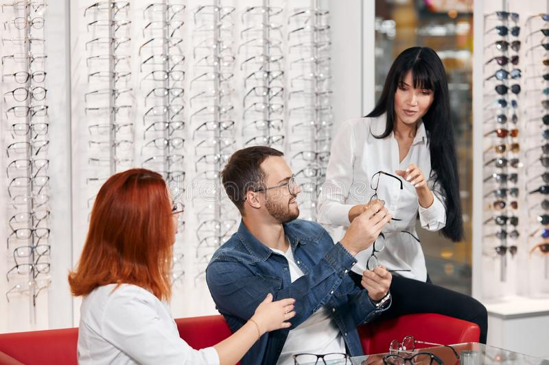 Two women presenting new models of glasses to a bearded cheerful client royalty free stock photo