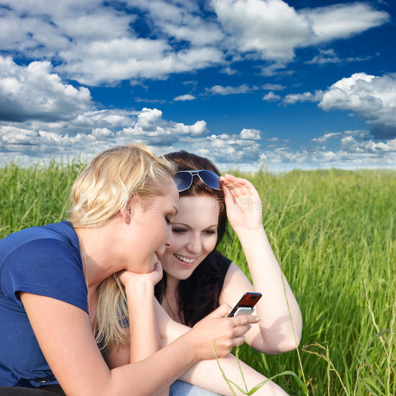 Two women reading sms. Two young women reading sms message on mobile phone stock images