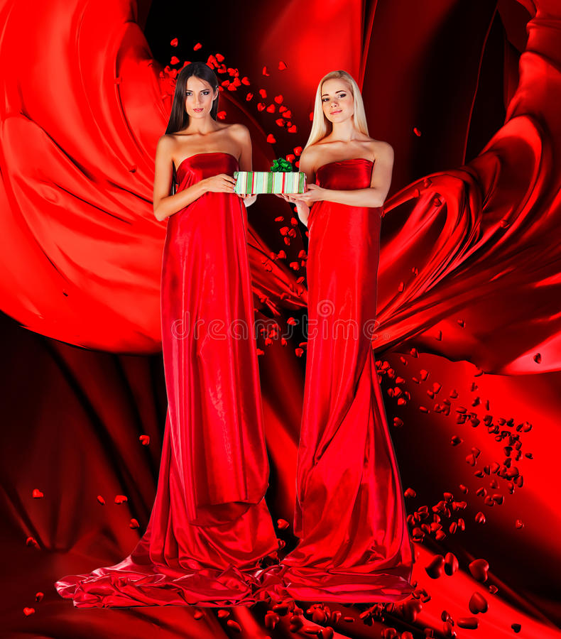 Two women in red dress with present in hands. On red drapery royalty free stock photography