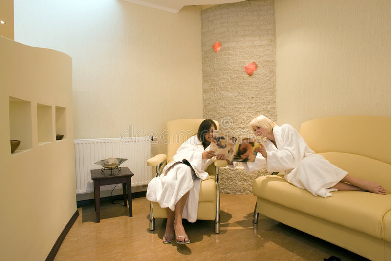 Two women at resort spa. A view of two women lounging in white bathrobes in a waiting room at a luxurious resort spa stock photo