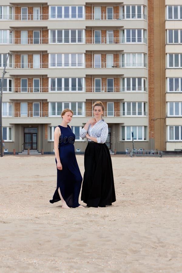 Two women beach sand apartment building, De Panne, Belgium. Two women in retro dresses at the beach in front of a art nouveau apartment building in De Panne stock photo