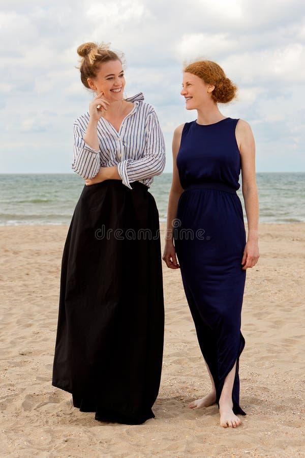 Two women beach sand sea talking, De Panne, Belgium. Two women in retro dresses talking on the beach at the sea in De Panne, Belgium royalty free stock image
