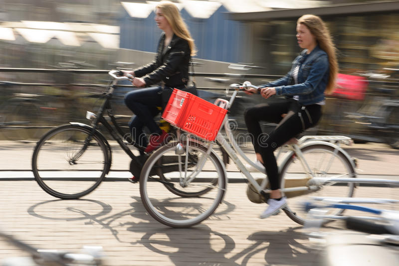 Two Women Ride their bikes to work in Amsterdam, Netherlands stock photo