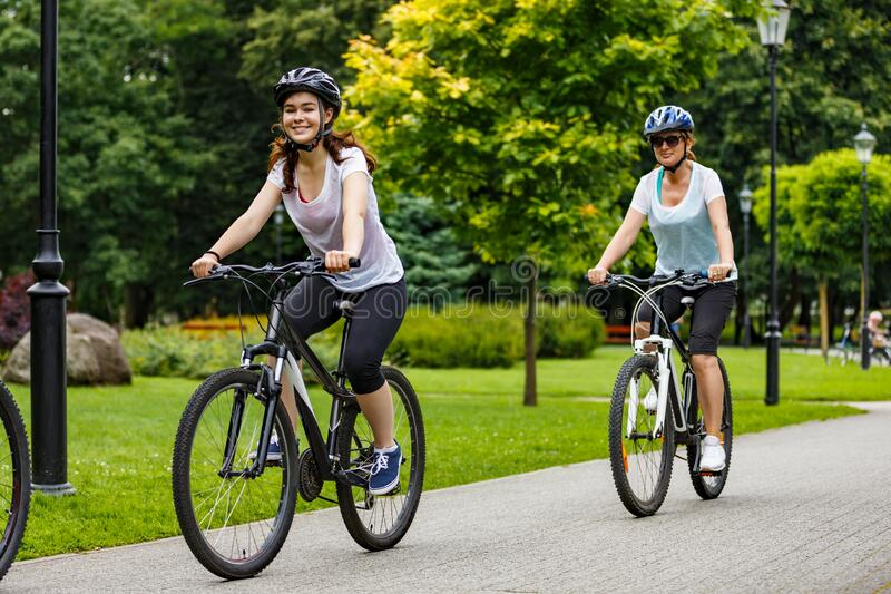 Two women riding bicycles together in summer park stock photos