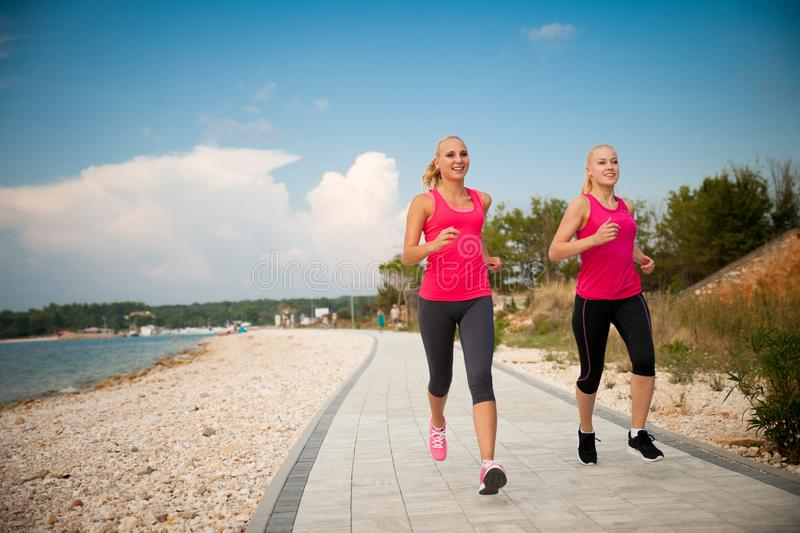 Two women athlets running on the beach - early morning summer w stock photos