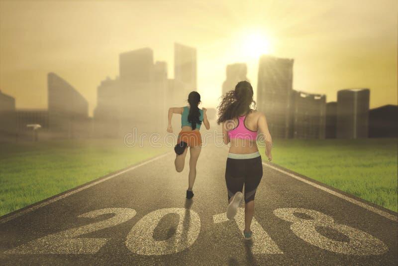 Two women running toward a city royalty free stock photos