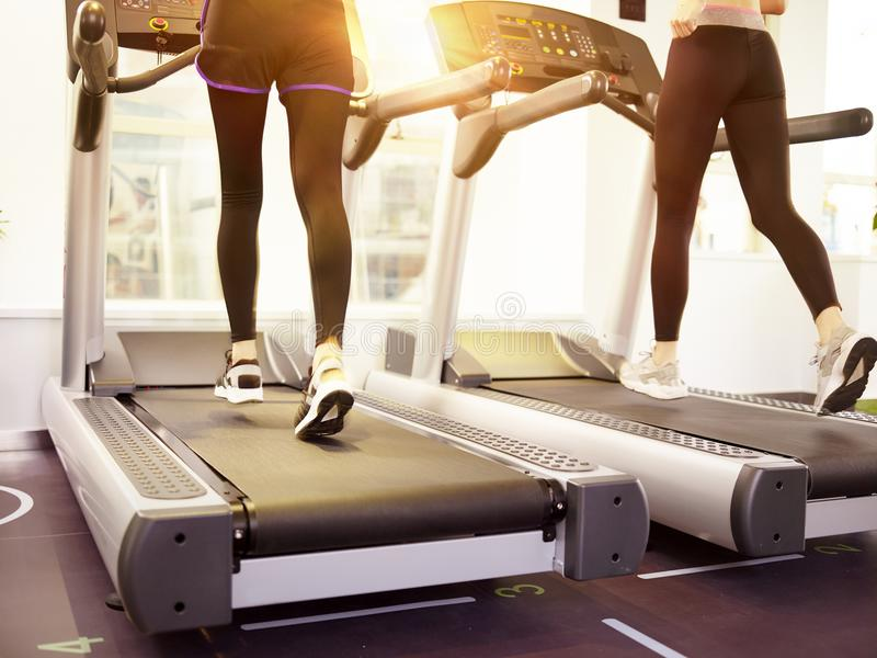 Two women running on treadmill in gym royalty free stock images